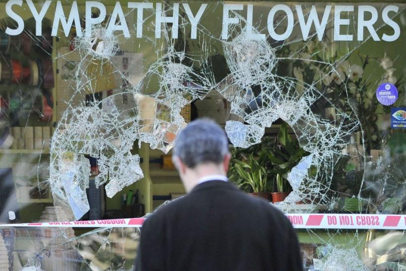A man looks at a looted florist shop in Ealing in west London.