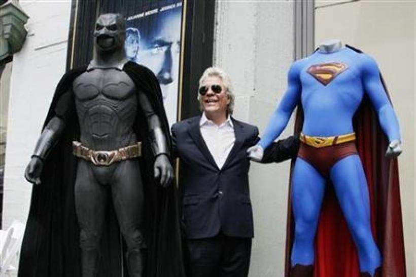 Film producer Jon Peters poses with a Batman (L) and Superman (R) costume after ceremonies unveiling his star on the Hollywood Walk of Fame in Hollywood