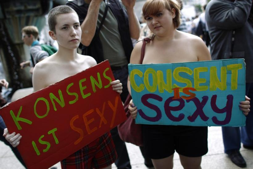 Women hold placards during a SlutWalk rally against sexual abuse and inequality in central Berlin