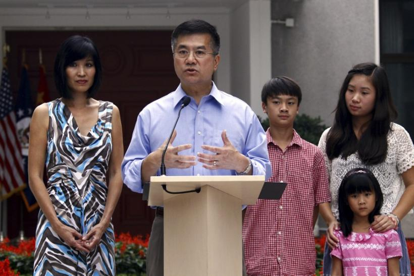 Locke, new U.S. ambassador to China, stands with his family outside their residence as he speaks to the media in Beijing