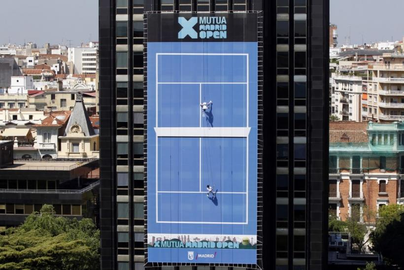 Acrobats perform a vertical tennis match over the facade of a building to promote the upcoming Madrid Masters tennis tournament in Madrid