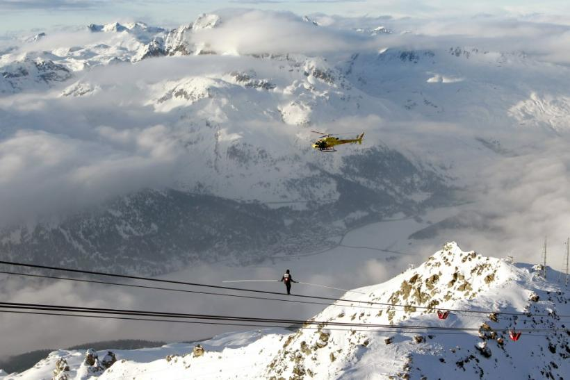 The village of Silvaplana is seen in the background as Swiss acrobat Freddy Nock balances down on the cable of a funicular on the Mount Corvatsch (3,303 m/9,908 ft)near the Swiss mountain resort of St. Moritz