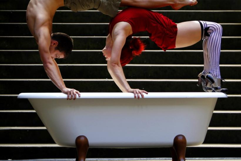 Fernando Dudka (L) and Masha Terentieva, acrobats from 'Soap, The Show', pose for photographers over a bathtub during a media viewing for their performances in the Edinburgh Fringe Festival in Scotland