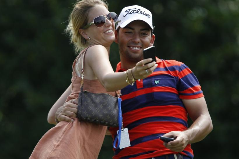 Larrazabal of Spain and his girlfriend Gala Ortin take a photograph on the ninth hole during a practice round for the 93rd PGA Championship golf tournament at the Atlanta Athletic Club in Jones Creek, Georgia