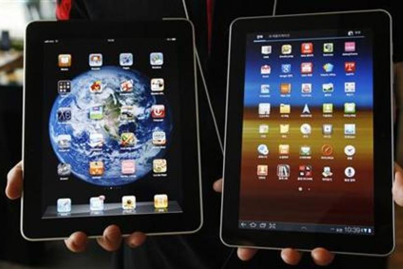 An employee of South Korean mobile carrier KT holds a Samsung Electronics' Galaxy Tab 10.1 tablet and Apple Inc's iPad tablet as he poses in Seoul