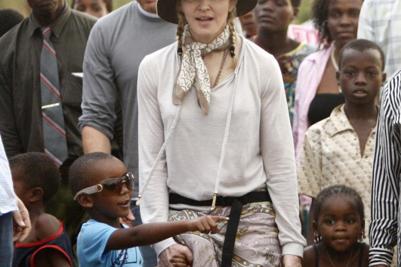 Madonna walks with her adopted children, David (L) and Mercy at the Mphandula Child Care Centre, about 47 km (29 miles) west of Lilongwe, October 29, 2009.