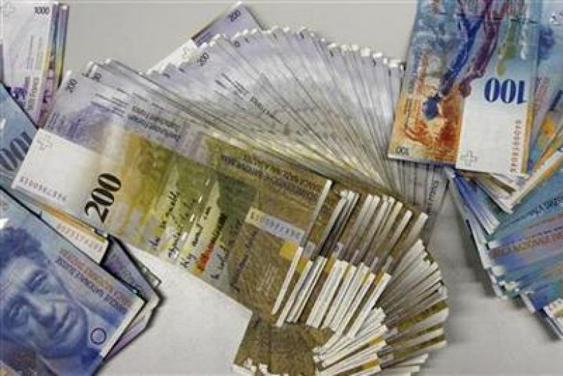 Swiss Franc banknotes of several values lie on a table before being sorted in a money counter in a Bank in Zurich