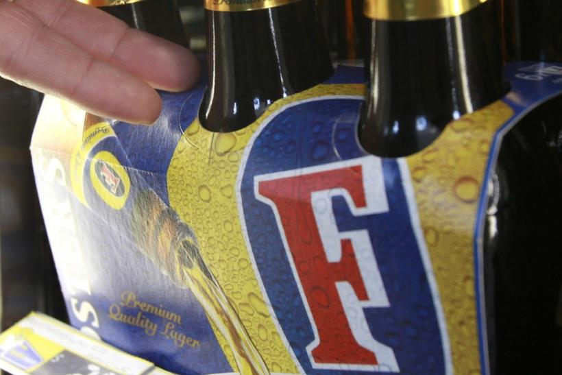 A customer takes a six-pack of Foster's beer from the fridge at a liquor store in Melbourne