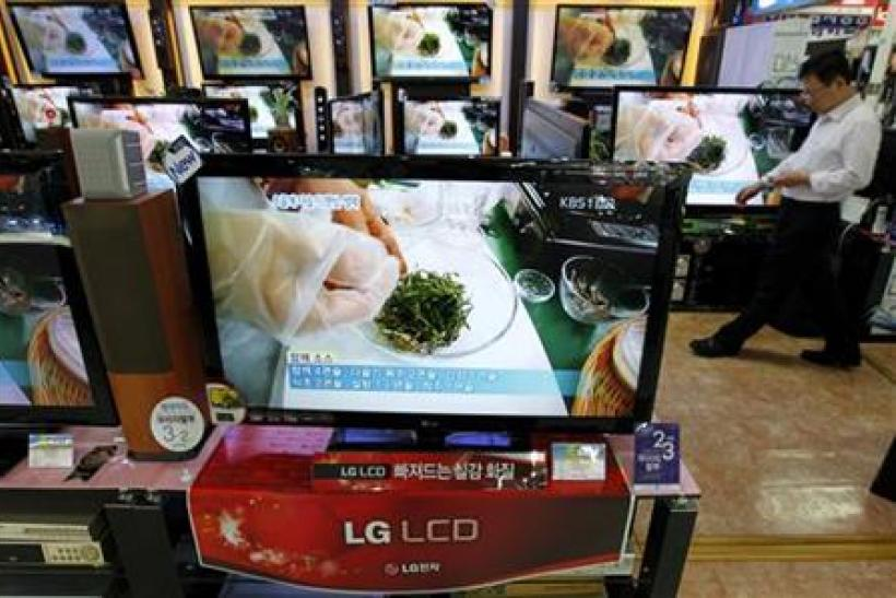 An employee of an electronics shop works behind an LG Electronics' LCD television set in Seoul