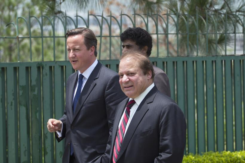 Pakistan's Prime Minister Nawaz Sharif (R) smiles and talks with his British counterpart David Cameron (L) as they leaves a joint news conference in Islamabad June 30, 2013