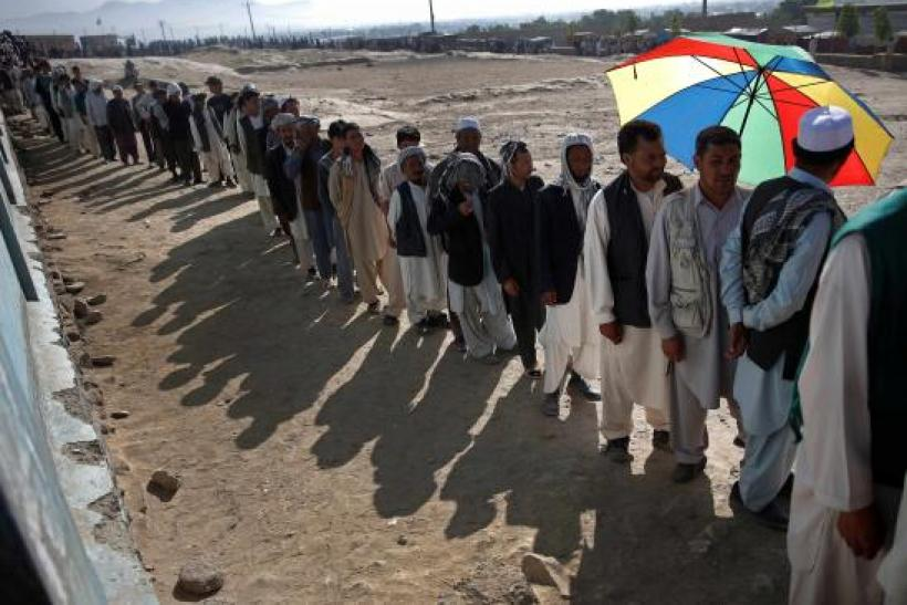 Afghan men line up to cast their votes at a polling station in Kabul June 14, 2014.