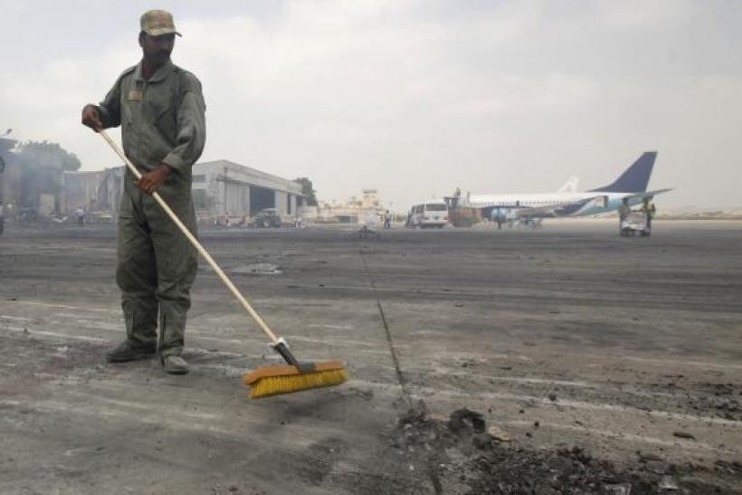 A man clears debris from the tarmac of Jinnah International Airport, after Sunday's attack by Taliban militants on Sunday, in Karachi June 10, 2014.