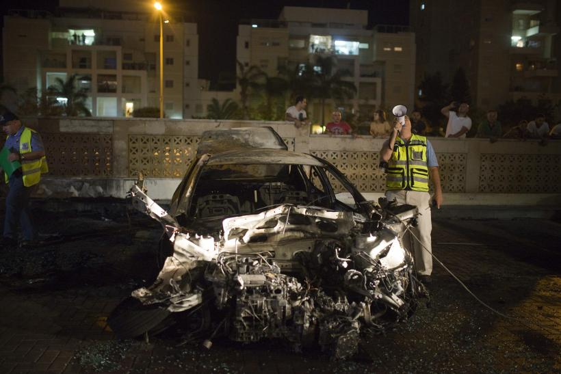Israeli security beside bombed car
