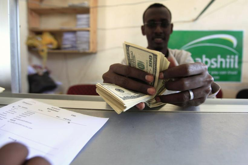 "A worker counts U.S. dollars as he serve a customers at a Dahabshiil money transfer office in ""Kilometer Five"" street of Soobe village, southern Mogadishu"