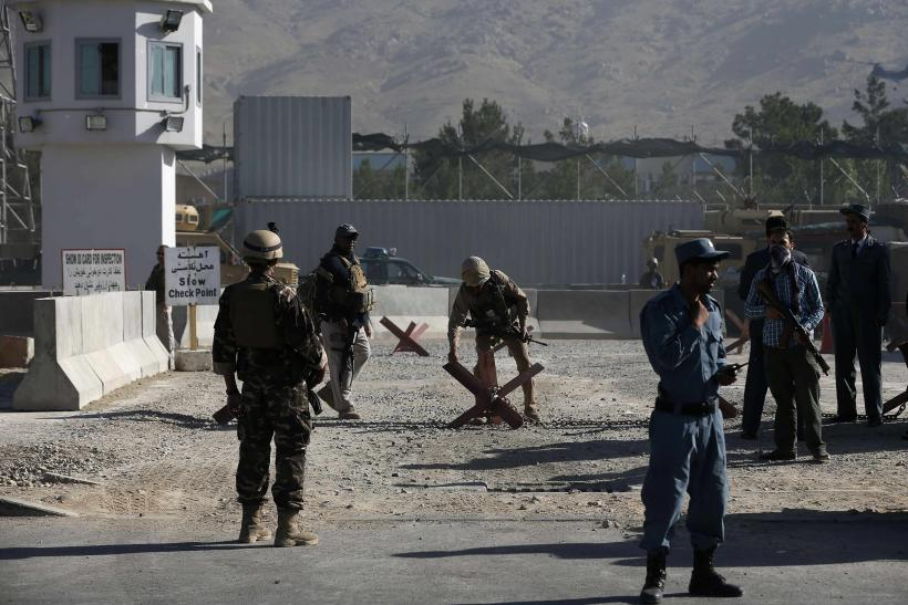 Afghan and foreign security personnel stand guard at the site of a blast, outside the counter-narcotics office near the Kabul International Airport July 22, 2014