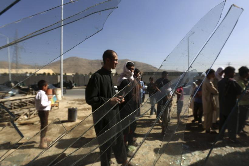 Afghans are seen through broken glass at a shop at the site of a blast, outside the counter-narcotics office near the Kabul International Airport July 22, 2014