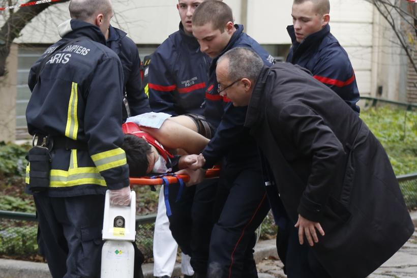 Firemen carry one of the victims away from the scene.