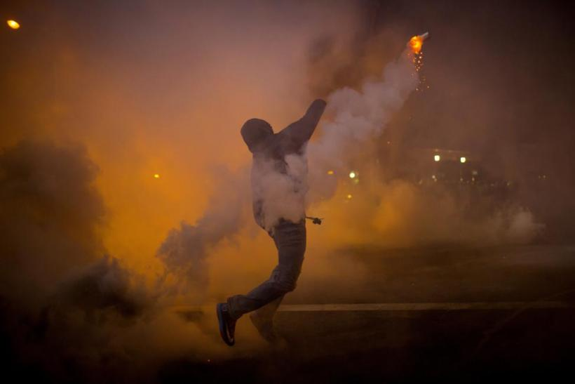 Baltimore protester throws gas cannister back at cops