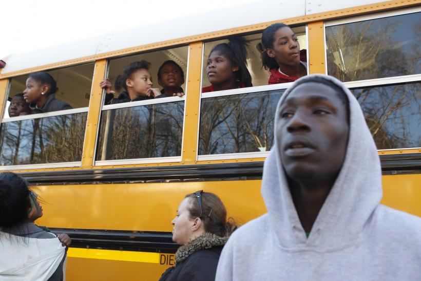 Children look for their parents from a school bus near Price Middle School following a shooting at the school in Atlanta, Georgia, January 31, 2013.