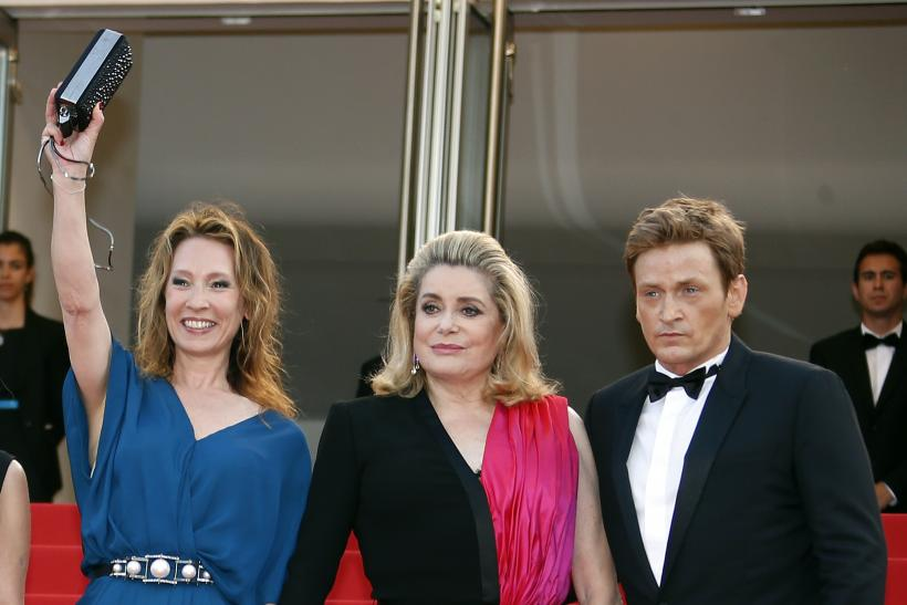 """[8:34] (L-R) Director Emmanuelle Bercot, cast members Catherine Deneuve and Benoit Magimel pose on the red carpet as they arrive for the opening ceremony and the screening of the film """"La tete haute"""""""