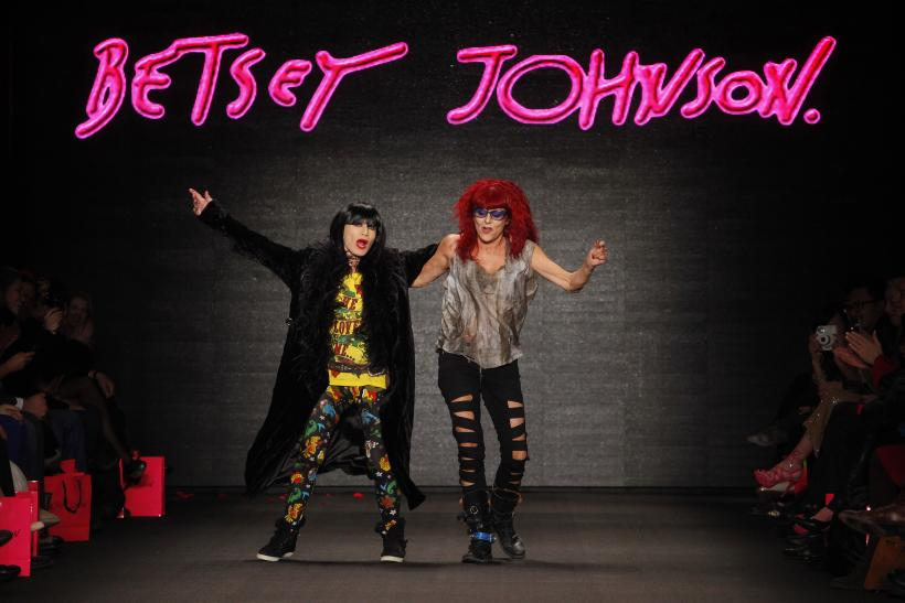 [12:07] Designers Betsey Johnson (L) and Patricia Field dance on the runway after Johnson's Fall/Winter 2011 collection show