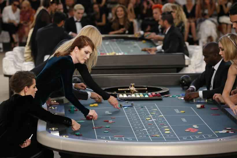 [8:27] Actress Julianne Moore (L) presents a creation by German designer Karl Lagerfeld as part of his Haute Couture Fall Winter 2015/2016 fashion show for French fashion house Chanel at the Grand Palais