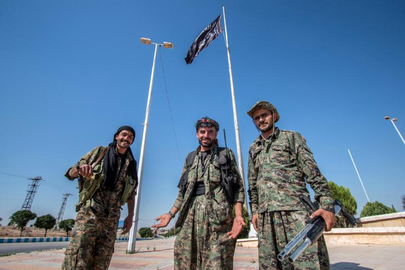 People's Protection Units (YPG) fighters stand near an Islamic State flag