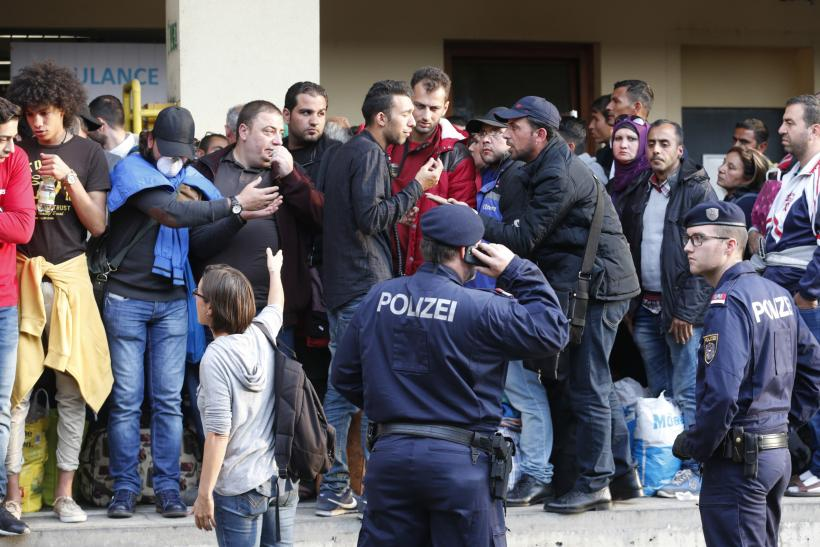 Refugees and police at a train platform in Vienna, Austria