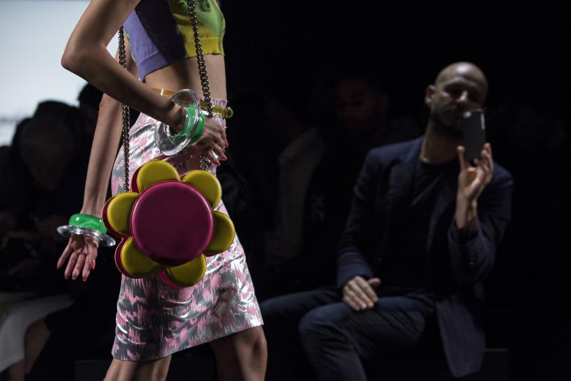 [12:05] An audience member looks on as a model presents a creation from the Jeremy Scott Spring/Summer 2016 collection