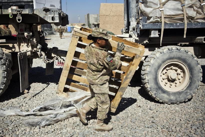 A female soldier carries a pallet passed a truck in Afghanistan