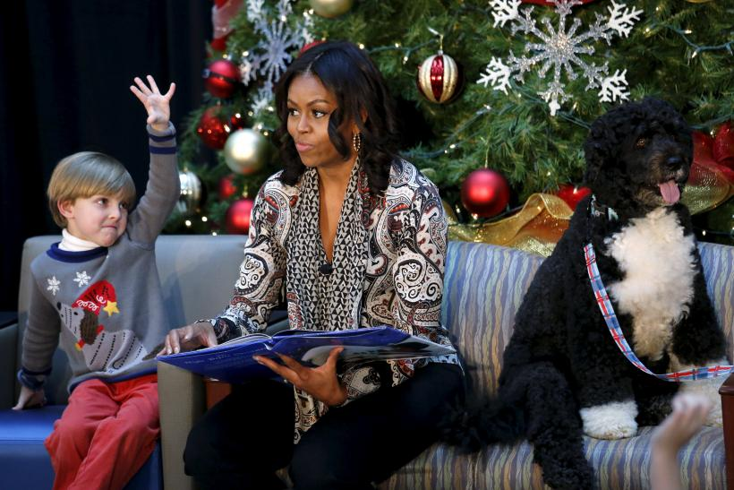 "Patient Stephen Orzechowski, 6, raises his hand as First Lady Michelle Obama reads ""T'was the Night Before Christmas"" to children during her visit to Children's National Health System"