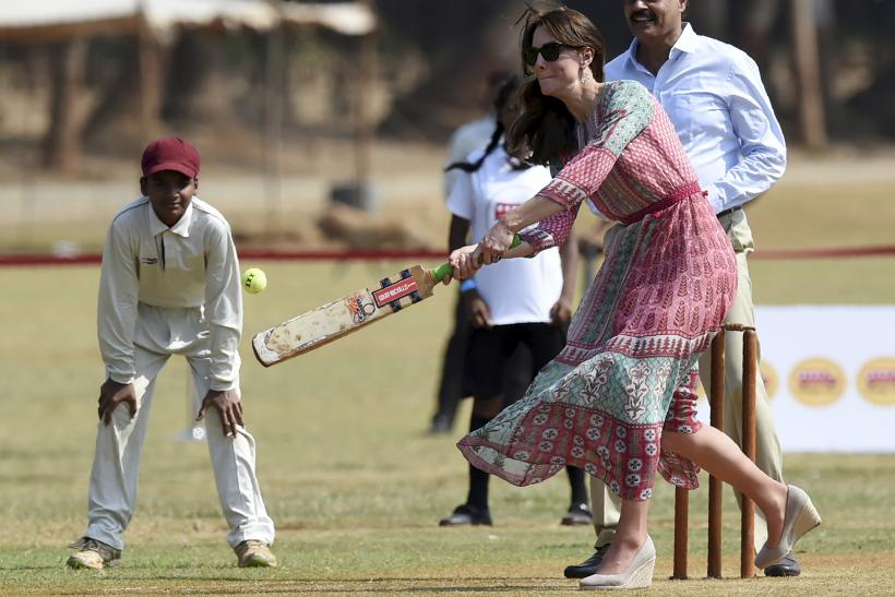 Catherine, Duchess of Cambridge, is watched by former Indian cricketer Dilip Vengsarkar (R)