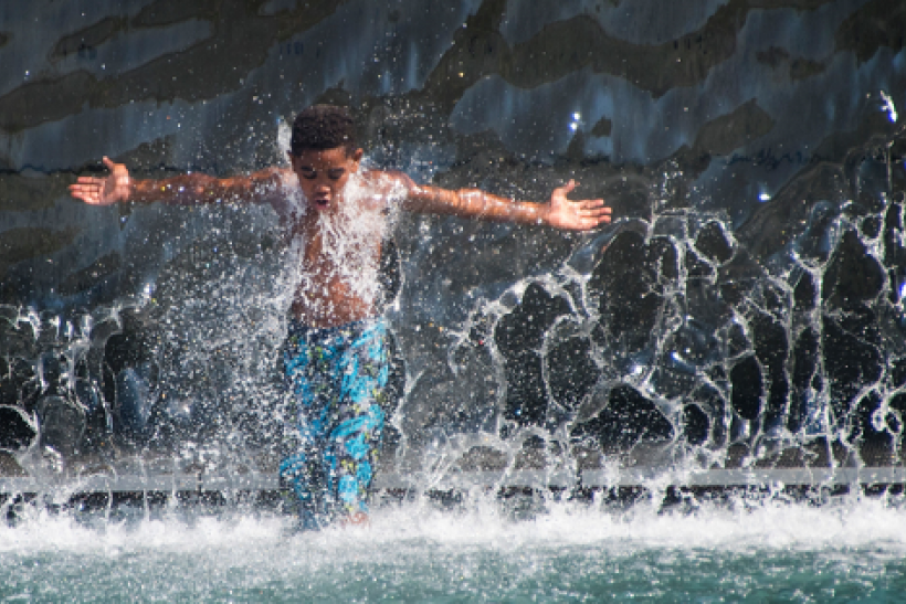 A boy walks through a waterfall on July 25, 2016 while playing in the water at The Yards Park in Washington, DC, as a heat wave rolls across the area