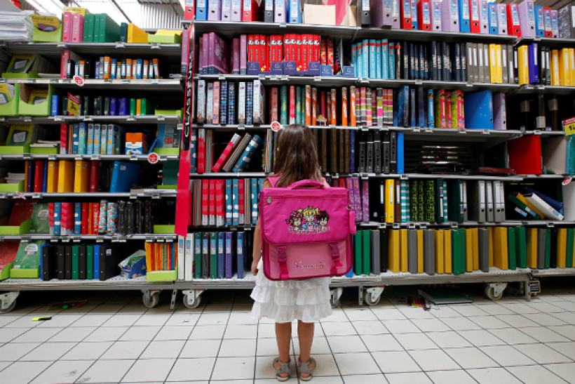 A young girl looks at school stationery in a supermarket in Nice August 23, 2012.