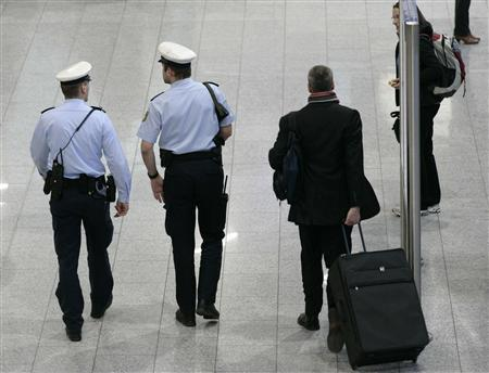 Police officers observe the scene inside the main terminal of Frankfurt`s airport
