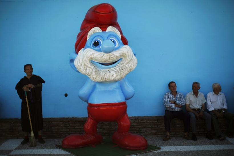 A man dressed up as Gargamel stands near a smurf statue during a promotional event in the Andalusian village of Juzcar