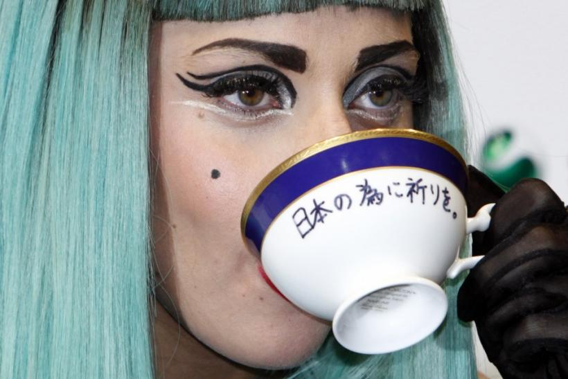 "Lady Gaga holds a teacup with the words ""Pray for Japan"" written on it as she attends a news conference in Tokyo."