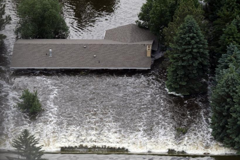 Strong water currents hit a house in Minot, North Dakota, as the Souris River spills over levees and dikes