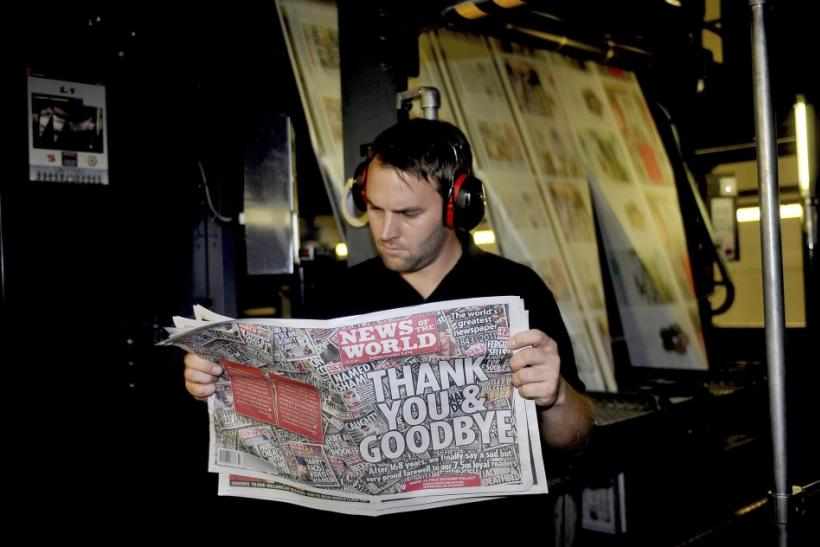 Printer James Bradley looks at a copy of the final edition of the News of the World in Waltham Cross