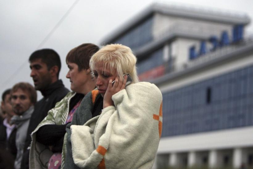 A survivor from the Bulgaria tourist boat, which sank on the Volga river, wraps herself with a blanket while talking on the phone after the arrival at the port of Kazan