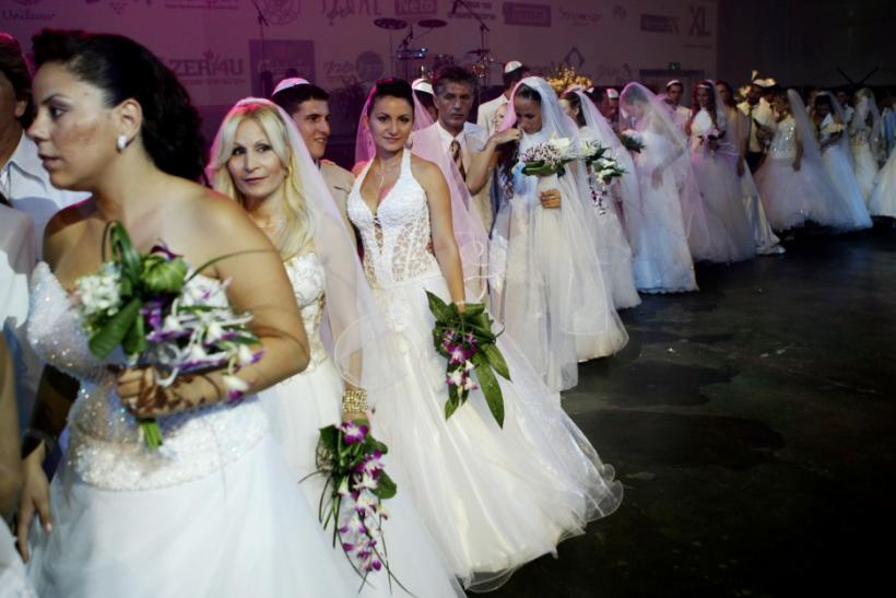 Brides and grooms take part in a mass wedding for 32 couples from areas of northern Israel skirting the Lebanese frontier, in Tel Aviv August 14, 2006.