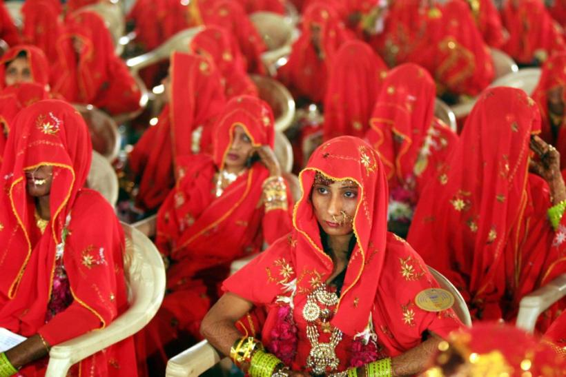 Indian Muslim brides sit during a mass wedding ceremony in the western Indian city of Ahmedabad March 10, 2007. A total of 163 Muslim couples from various city slums of Ahmedabad took wedding vows during the two days mass marriage ceremony organized by a