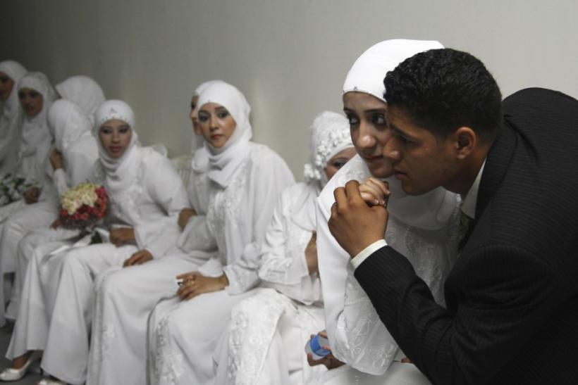 A Palestinian bride poses for a picture with her groom during a group wedding ceremony in Sidon, southern Lebanon, July 18, 2010. Fifty Palestinian couples participated in the group wedding ceremony organized by the Hamas movement in Lebanon.