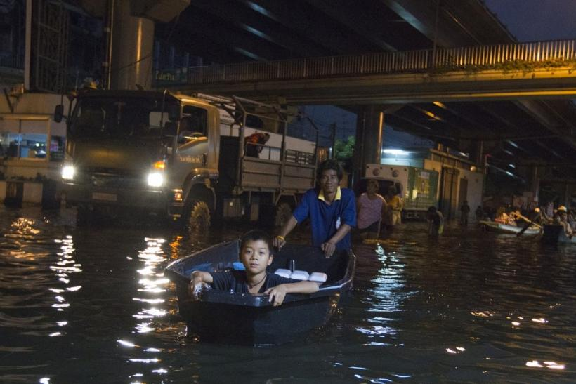 A man uses a boat to transport a boy through the flooded streets of Bang Phlat district in Bangkok on November 1, 2011.