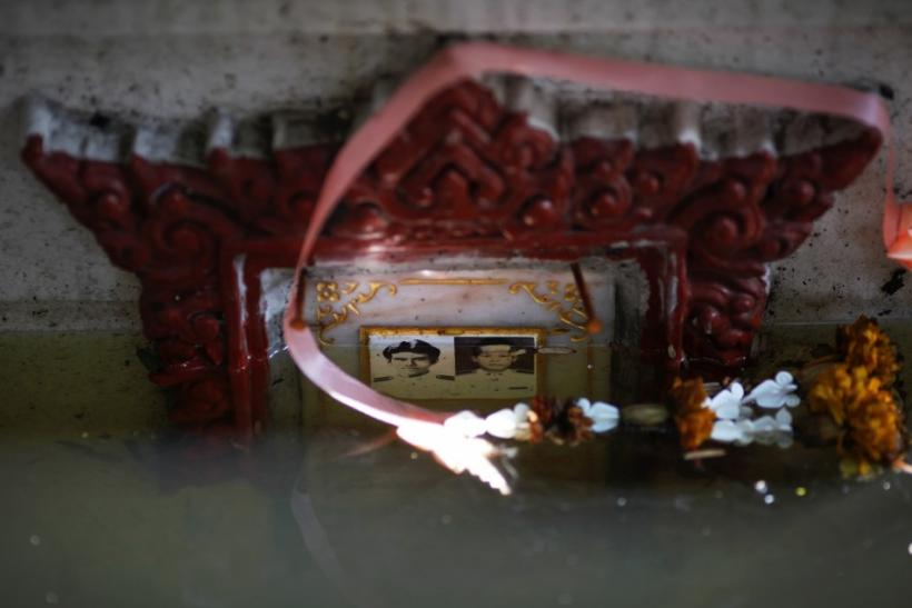 A submerged grave with pictures is seen at a flooded Buddhist temple in Bangkok November 1, 2011.