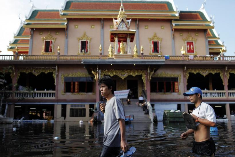 People wade through water at a Buddhist temple where hundreds of floods victims found shelter in Bangkok November 1, 2011.