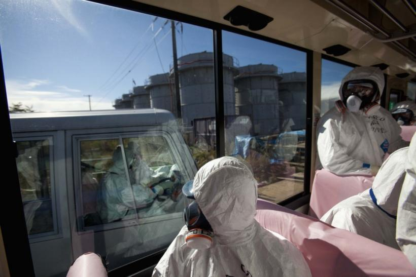 Officials from the Tokyo Electric Power Co. and journalists look out from bus windows as workers pass by in a van inside the grounds of the crippled Fukushima Daiichi nuclear power plant