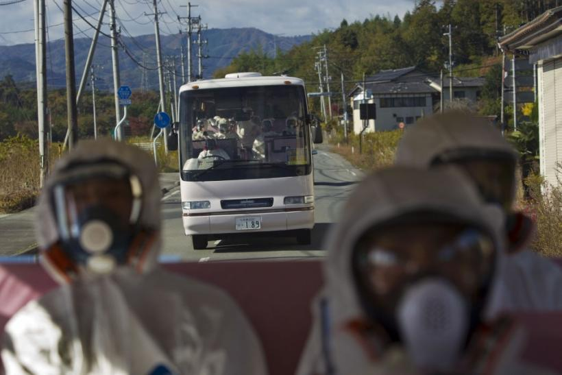 Japanese officials wearing protective suits and masks ride in the back of a bus