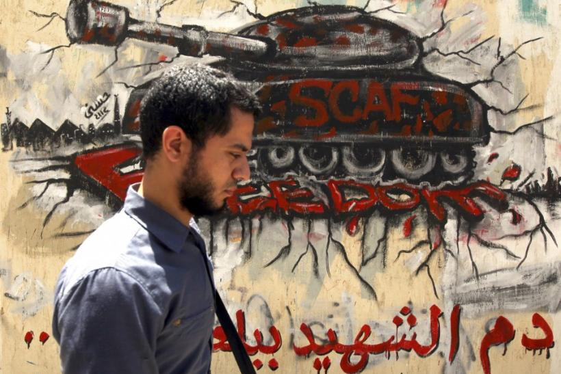 An Egyptian man walks in front of a wall sprayed with graffiti depicting a tank, as a protest against the ruling Supreme Council of the Armed Forces (SCAF), near Tahrir Square in downtown Cairo May 16, 2012.