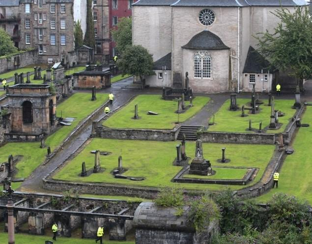 Police stand guard in the church graveyard as preparations begin for the wedding of Zara Phillips and Mike Tindall inside the Canonngate Kirk in Edinburgh